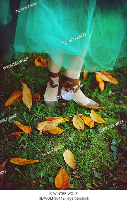 Young woman wearing dancing shoes Cropped photo of a dancer wearing a green tulle skirt with her slippers in some pretty autumn leaves