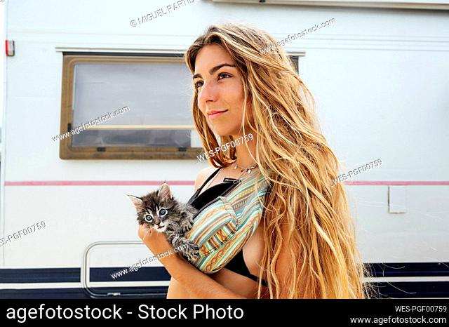 Thoughtful woman with kitten in waist pack