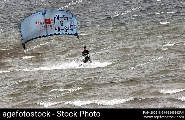 18 February 2020, Berlin: At wind speeds of up to 59 km/h and temperatures of around seven degrees Celsius, a kitesurfer moves over the churning water of Lake...