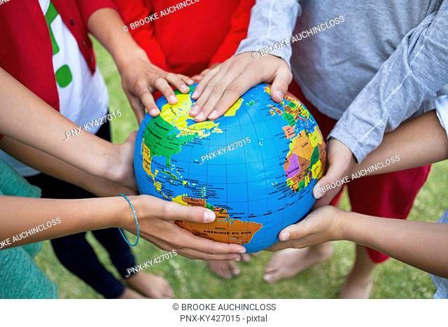Close-up of friends holding a globe