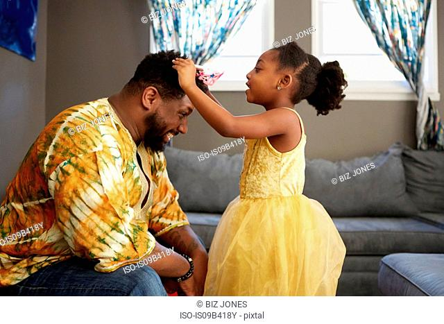 Girl in princess costume putting tiara on father in living room