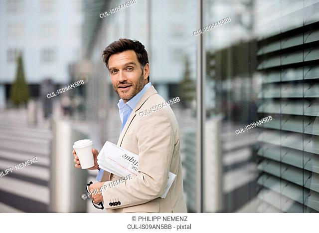Mature businessman walking outside city office carrying newspaper