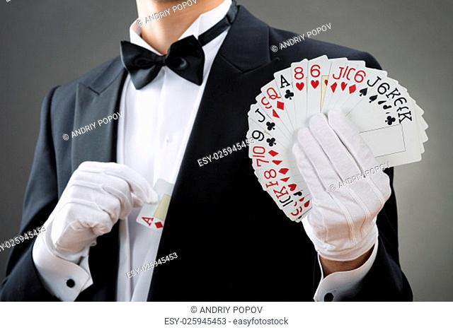 Midsection of magician showing fanned out cards against gray background