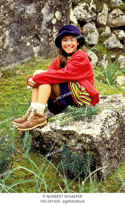 portrait, Indio girl, 12 years, wearing red jacket and woven skirt with blue velvet hat rests laughing on a rock  - GERMANY, 27/07/2003