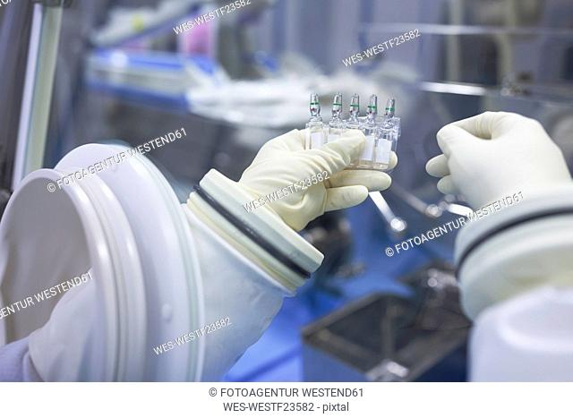 Scientist holding vials in insulator laboratory