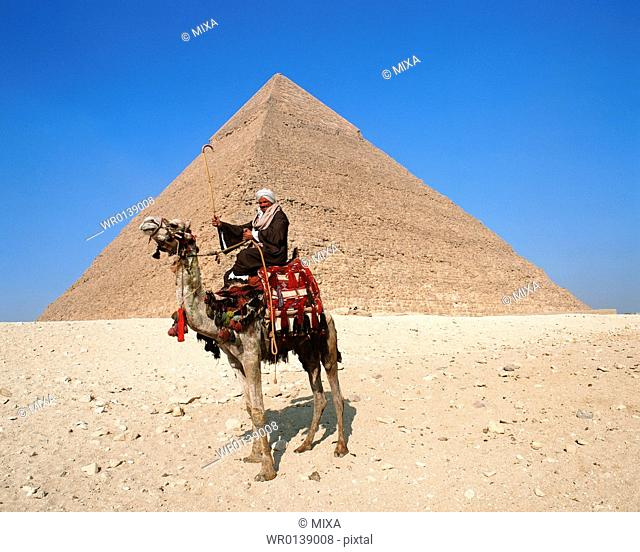 Side view of a camel rider in front of pyramid, Giza, Egypt