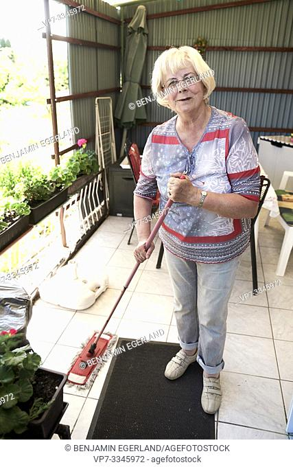 senior housewife woman mopping terrace at allotment garden bungalow