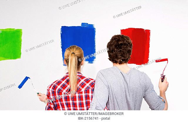 Young couple sampling various wall paint colours