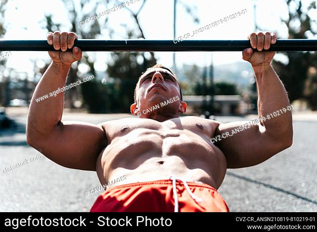 Portrait of a muscular athlete doing a barbell pull-up in a park