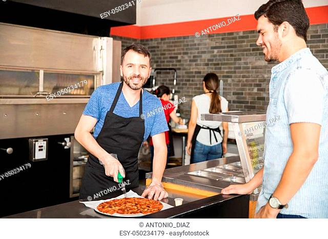 Happy chef cutting pizza in slices looking at camera while handsome customer waits for pizza in pizza shop