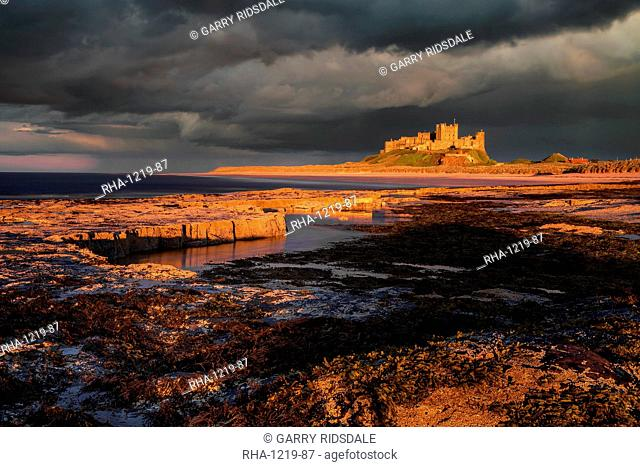 A storm passes behind Bamburgh Castle with the last light of the day illuminating the rocky shoreline and castle, Northumberland, England, United Kingdom