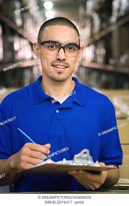 Hispanic man with clipboard in warehouse