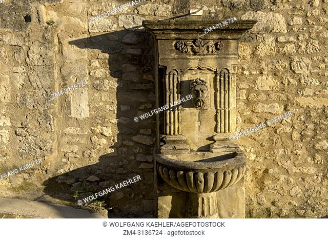A village scene with a fountain in the hillside village of Lacoste in the Luberon in the Provence-Alpes-Cote d Azur region in southeastern France