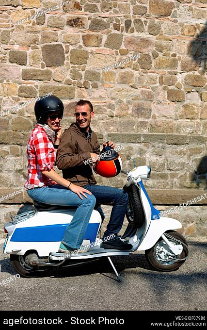 Laughing couple on motor scooter in front of stone wall, Italy