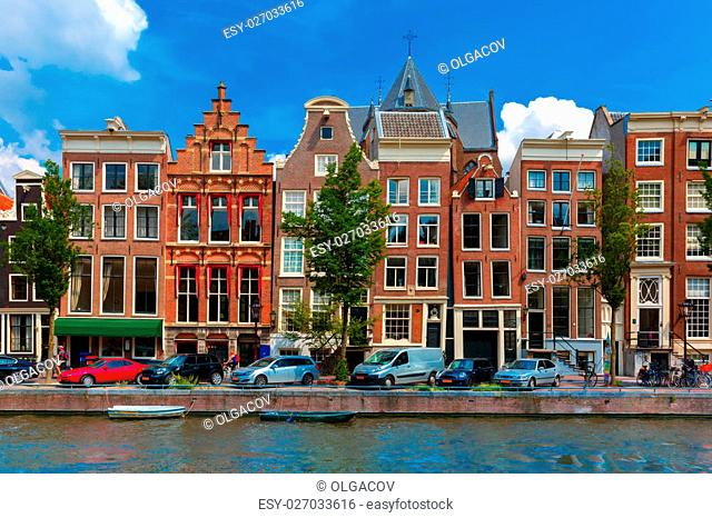Night city view of Amsterdam canal, typical dutch houses and boats, Holland, Netherlands