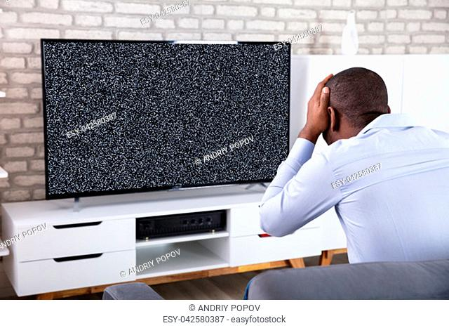 African Man Touching His Head Near Television Showing No Signal