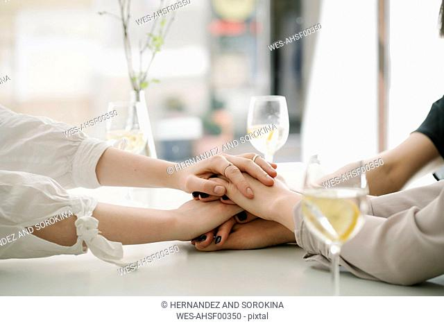 Close-up of three women stacking hands on table in a restaurant