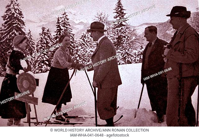 Adolf Hitler 1889-1945. German politician and the leader of the Nazi Party with skiers at his mountain retreat at Obersalzberg