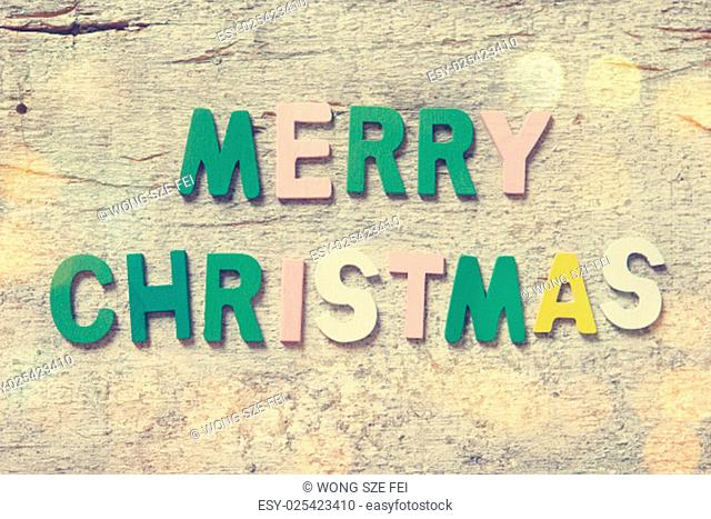 "The colorful words """"MERRY CHRISTMAS"""" made with wooden letters on old wooden board"