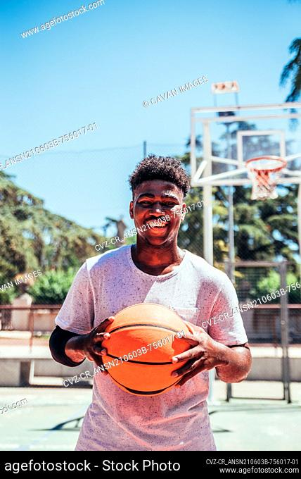 Portrait of a black African-American boy smiling and holding a basketball against his chest on an urban basketball court