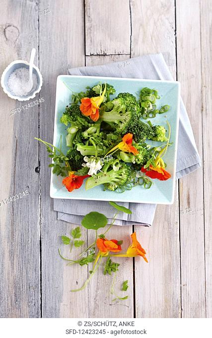 Warm broccoli salad with fresh wild herbs and edible flowers