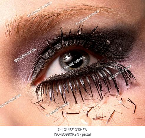 Female eye with pieces of eyelash and tears