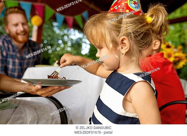 Little girl eating cake on a birthday garden party
