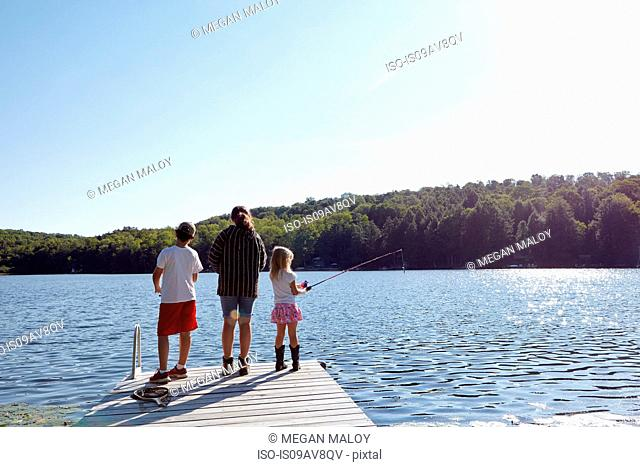 Children fishing on pier by lake, New Milford, Pennsylvania, US