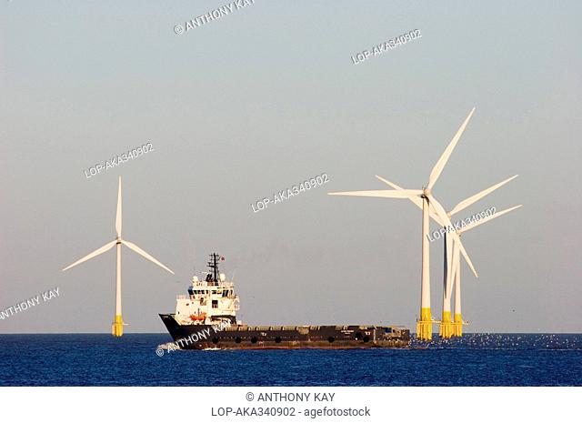 England, Norfolk, Great Yarmouth, A cargo ship, the Olympic Provider passing in front of an offshore wind farm at Great Yarmouth in Norfolk