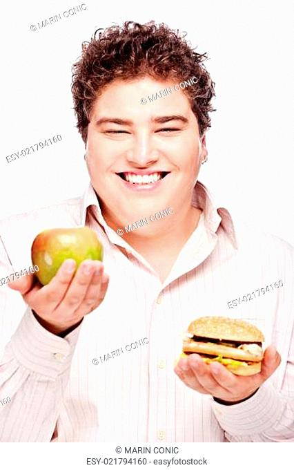Young chubby man holding apple and hamburger