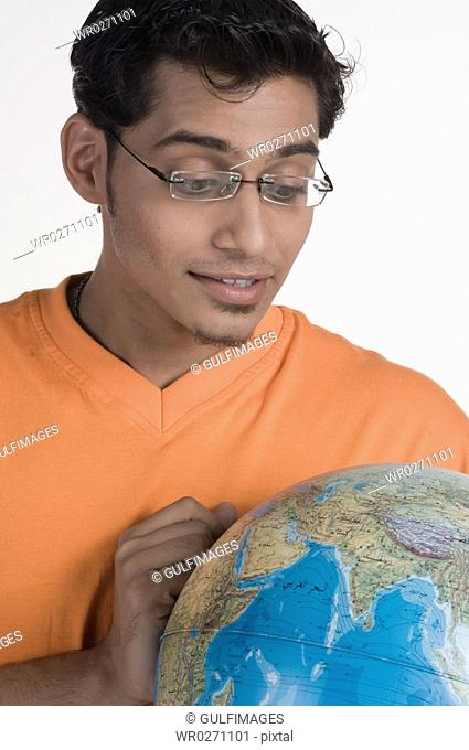 Young man with globe, close-up
