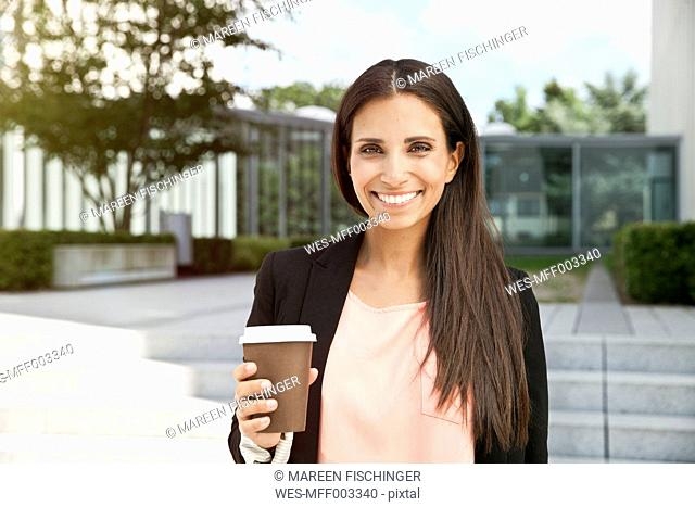 Portrait of smiling woman holding takeaway coffee outdoors