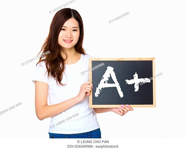 Woman with the chalkboard showing a A plus mark