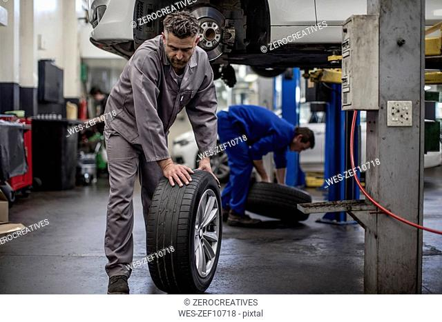 Car mechanics in a workshop changing tires
