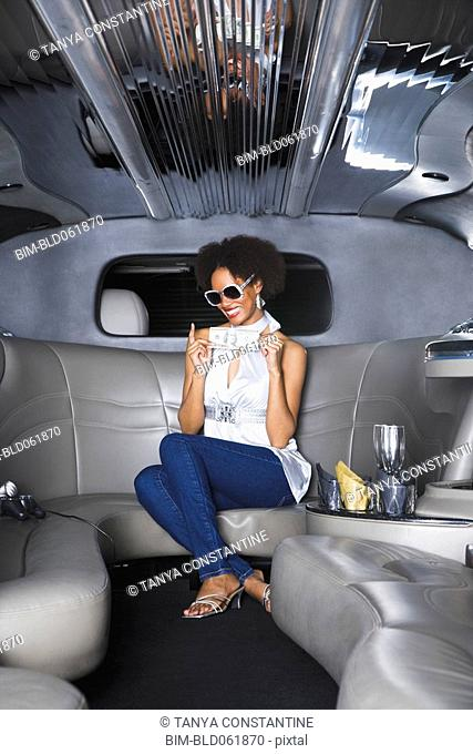 African woman holding money in limousine