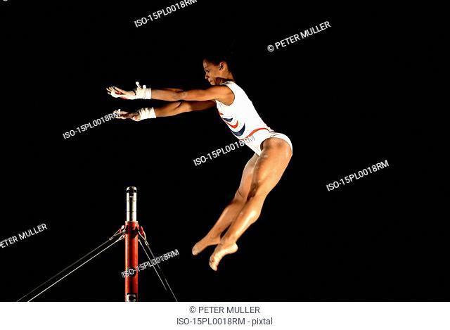 gymnast swinging to grab high bars