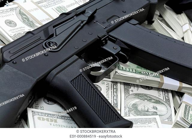 Close-up of black weapon lying on heap of hundred dollar bills