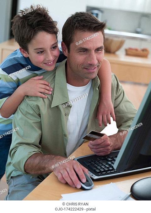 Man with credit card using computer with boy
