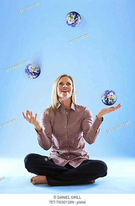 Young woman juggling globes in clouds