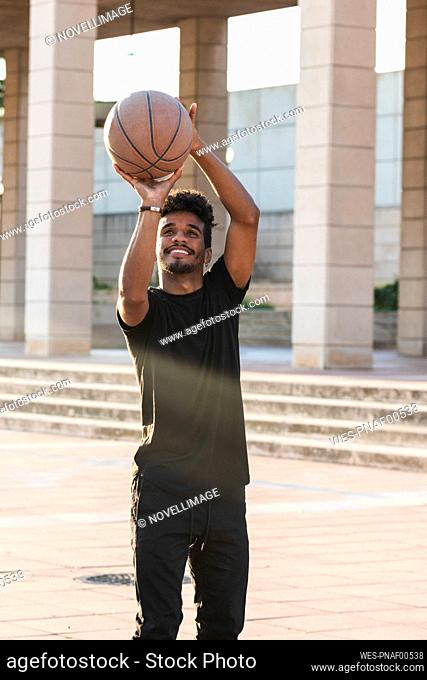 Smiling young man playing basketball in park during sunset