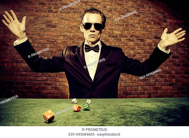 Excited gambling man throwing dice on a game table in a casino. Gambling, playing cards and roulette