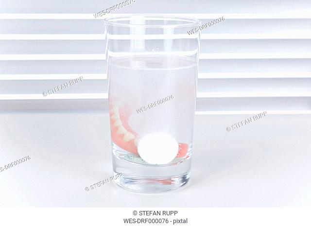 Germany, Freiburg, Dental prothesis in glass of water with cleaning tablets