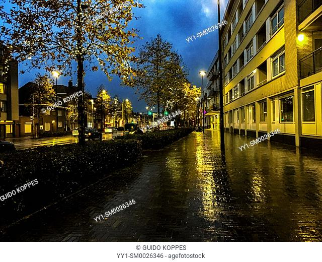 Tilburg, Netherlands. Down town residential street with apartment buildings, sidewalk and lights, during a fall season rainy evening at dusk
