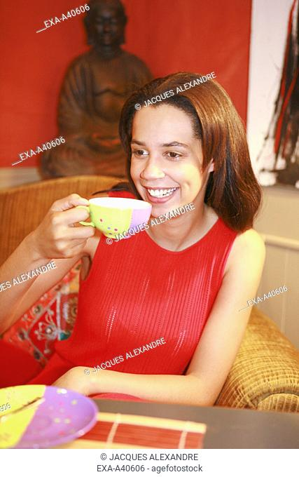 Young woman holding tea cup and smiling