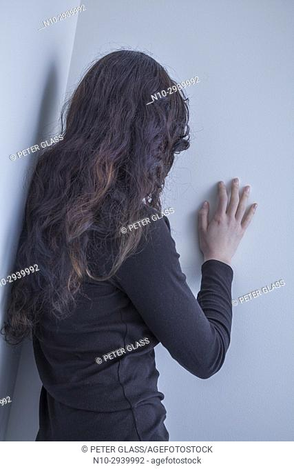 Teenage girl, back to camera, hand on a wall