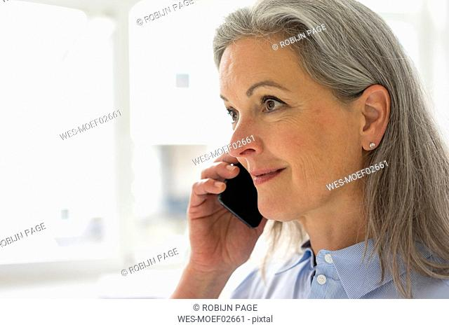 Portrait of mature businesswoman on the phone in office