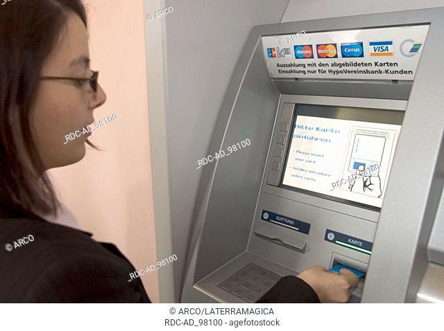 Woman at cash dispenser Germany cash point cash terminal bank