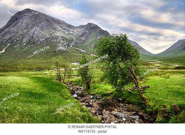 Stream to River Coupall valley with white cottage at foot of Stob Dhearg peak of Buachaille Etive Mor mountains Glen Coe Scotland UK