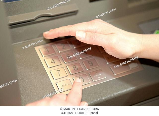 Woman covering keypad when entering PIN in cashpoint
