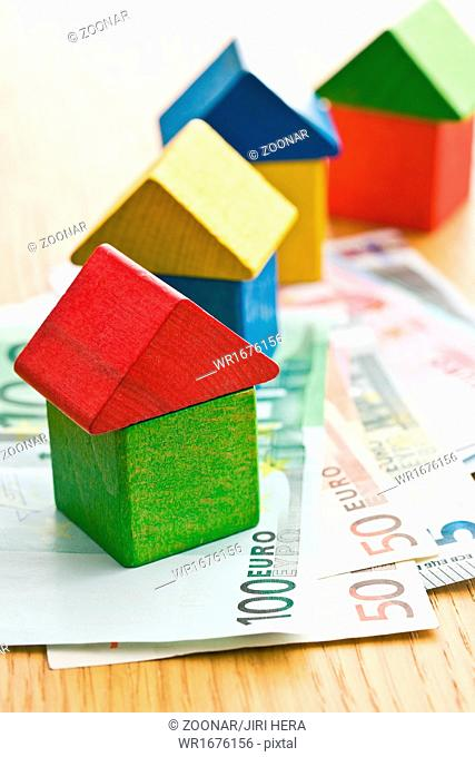 house made from wooden toy blocks with euro money